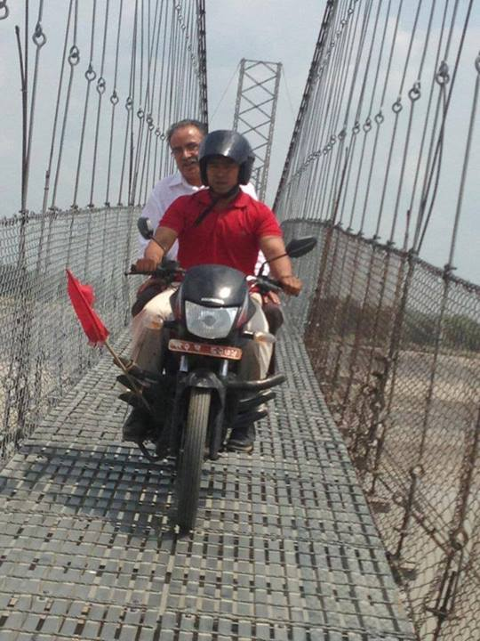 Prachanda on bike in the bridge